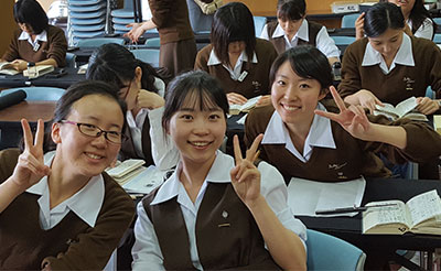 Three students pose for a picture in their classroom at Notre Dame Jogakuin Jr. and Sr. High School in Kyoto, Japan.