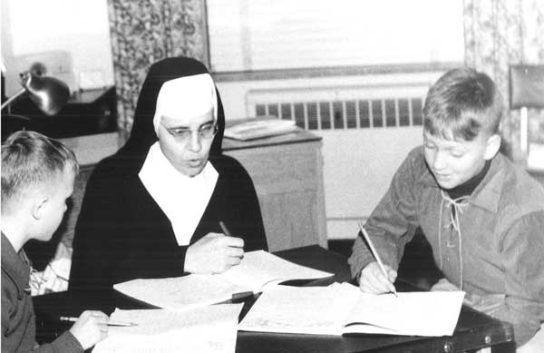 Sister Mary Donald Miller and two boys. Sister Mary Donald originally started the Good Counsel Learning Center.