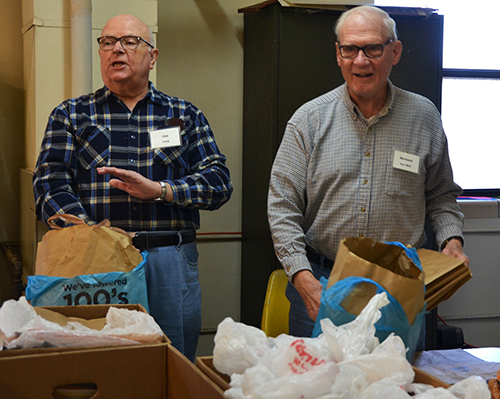 Two volunteers packing groceries at the Wellston Center.