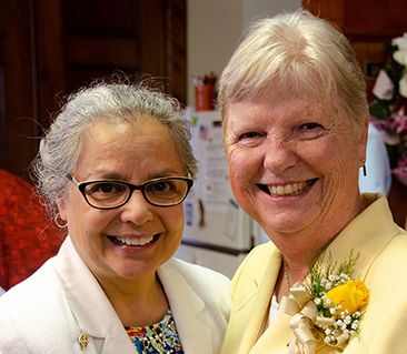 Sister pinning on the Jubilarian's flowers at the 2018 Jubilee at Sancta Maria in Ripa campus. Sisters Christine Garcia and Janet Crane.