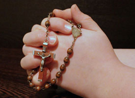 Image of praying hands holding rosary