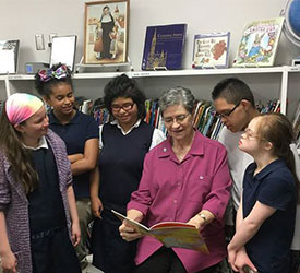 Sister Georgiann Wildhaber with students in the school library.
