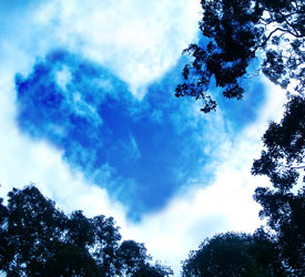 Clouds in sky forming blue heart.
