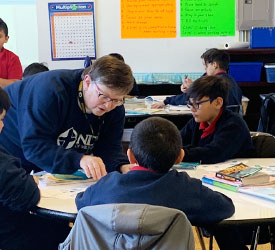 Sister Judy teaching to a group of boys around a table at the school Notre Dame of Milwaukee