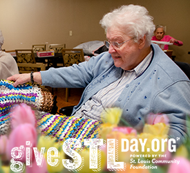 Sister Cordula Wekenborg shows off a plastic mat she made for the homeless. The logo for Give STL Day is also featured.