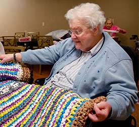 Sister Cordula Wekenborg shows off a plastic mat she made for the homeless.