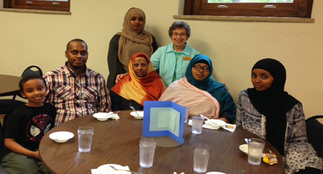 Sister Richarde Marie Wolf (back row; right) poses with two of the Refugee Outreach Program's students Zahra (front left of Sister Richarde Marie) and her mother, Adday (front right of Sister Richarde Marie), and their family attended the celebration.