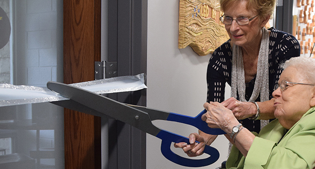 Donor Betty Mutza and Sister Benilda Dix cut the ribbon leading to one of the archives rooms at the SSND North American Archives blessing and dedication at Mount Mary University, Milwaukee, on June 2, 2018.