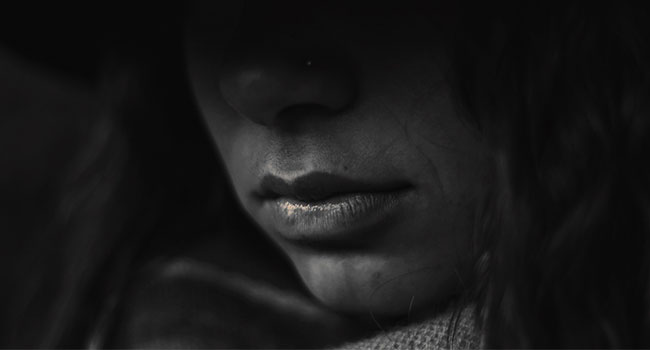 Black and white photo of a women's face showded in mistery. This photo is to represent a survivor of human trafficking