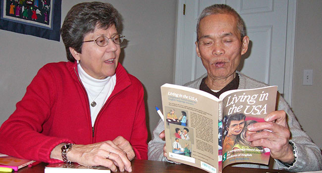 Sister Denay Ulrich teaches a Vietnamese man who was a colonel in the Vietnam War. He was at MORE to learn English