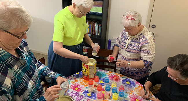 Sisters Jan Gregorcich, Pam Moehring, Elizabeth Swartz and Carol Dwyer work in an El Paso facility to fill baby bottles with formula to be distributed to tent cities in Mexico.