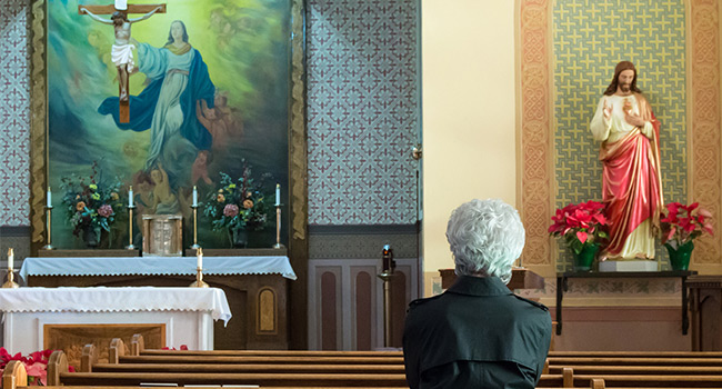 This is a photo of a women sitting in a church praying. A Jesus statue, the cross and a large painting of Mary is visable.
