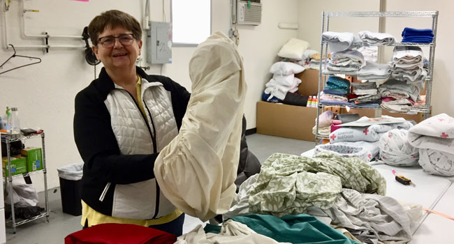 Associate Mariellyn Kuske is folding clothes during her volunteer time at Casa in El Paso.