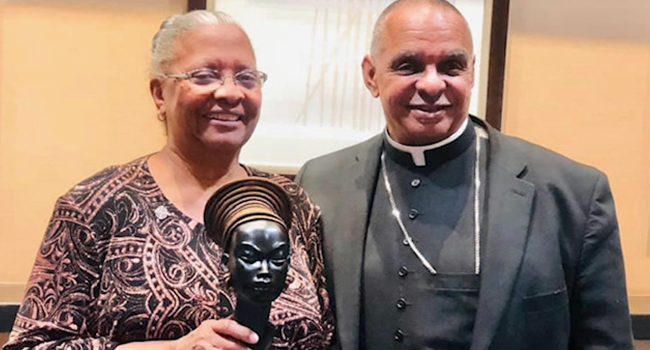 Sister Addie Lorraine Walker holds her Legacy Award from the 33rd Annual MLK Commission Inter-faith Worship Serviceaward, next to a priest.