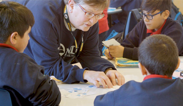 Sister Judy Fleisner reviews a math project with students at Notre Dame School of Milwaukee