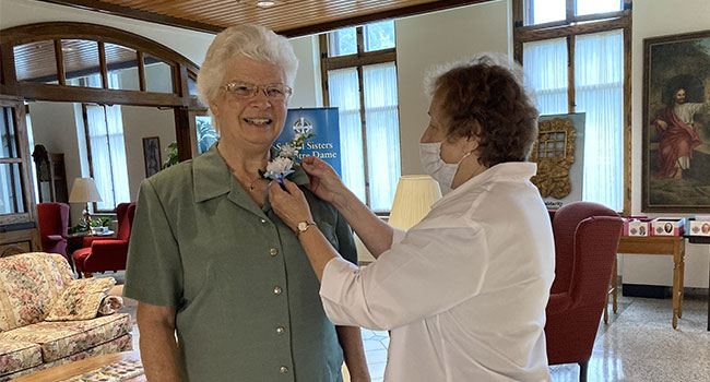 Sister Sue Von Bank, 60-year Jubilarian, and Sister Mary Ann Kuhn, Community Leader pinning flowers for an in-house Jubilee Celebration at OLGC.