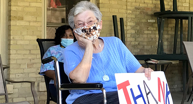 """Sisters sit outside with thank you sign for a """"car parade"""" during COVID-19 at Notre Dame of Elm Grove, Elm Grove, Wisconsin."""