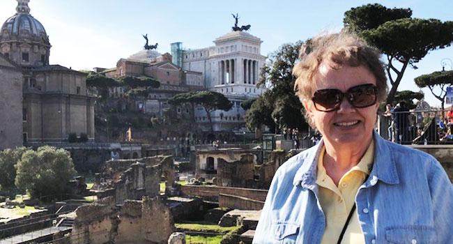 Sister Connie Schmidt is posing for a photo with a few historical buildings behind her in Rome.