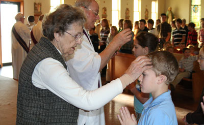 A sister places ashes on a student's forehead during the Ash Wednesday service at St. Martin Church in Milwaukee.