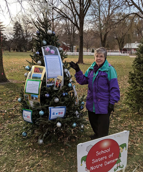 A picture of S. Monica Wagner with the 2017 Christmas tree decorated for the Kiwanis Holiday Lights in Mankato, Minnesota.