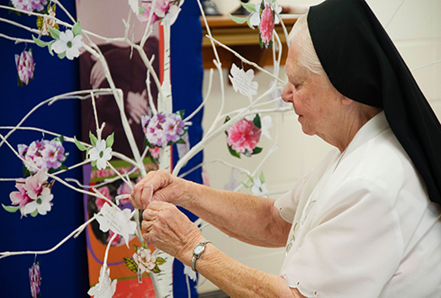 On September 21, 2019, sisters gathered for a celebration of gratitude and farewell to 145 years of SSND presences at Chatawa, Mississippi. Sister Gemma Marie places a printed flower on the remembrance tree, sharing her fondest moments at St. Mary of the