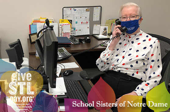 Sister Linda Jansen poses for a photo in the Resource Development Office at her desk in St. Louis. The image contains the Give STL Day logo, School Sisters of Notre Dame and boardered by Jubilee 2021 logo image.