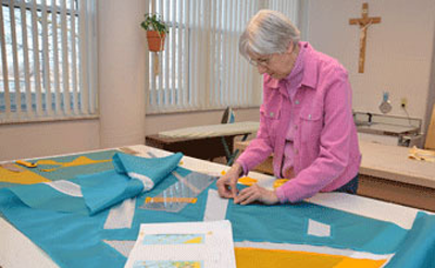 Sister Josephine Niemann works on a piece in Liturgical Fabric Arts.