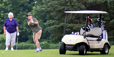 Golf tournament participants enjoying a day on the course.