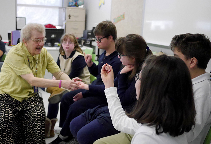 Sister Maureen Therese Mueller works with students at Notre Dame of Dallas.