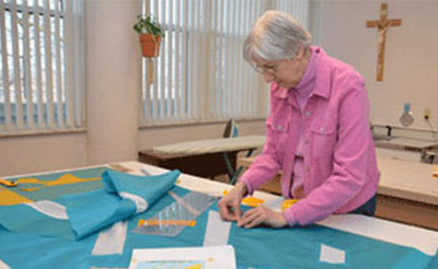 Sister Josephine Niemann working in Liturgical Fabric Arts located at Sancta Maria in Ripa in St. Louis.