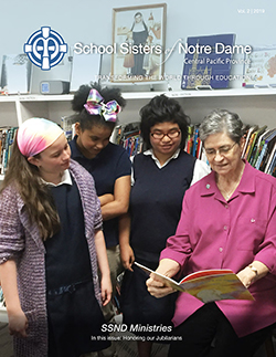 Sister Georgiann Wildhaber shares a book with students from the intermediate blue team at the Notre Dame School of Dallas. (L to R) Vivi Sellers, Christina Smith, Victoria Stevens, Sister Georgiann Wildhaber.