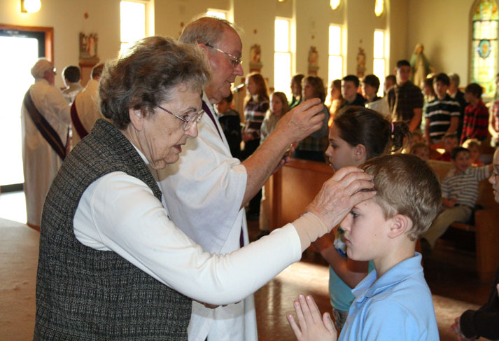 An SSND places ashes on a student's head at the Ash Wednesday service at St. Martin's in Milwaukee.
