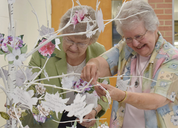 Sisteres Ancilla Roussel and Lorraine Landry place a memory flower on a tree in dedication and celebration of 145 years at St. Mary of the Pines in Chatawa, Mississippi.