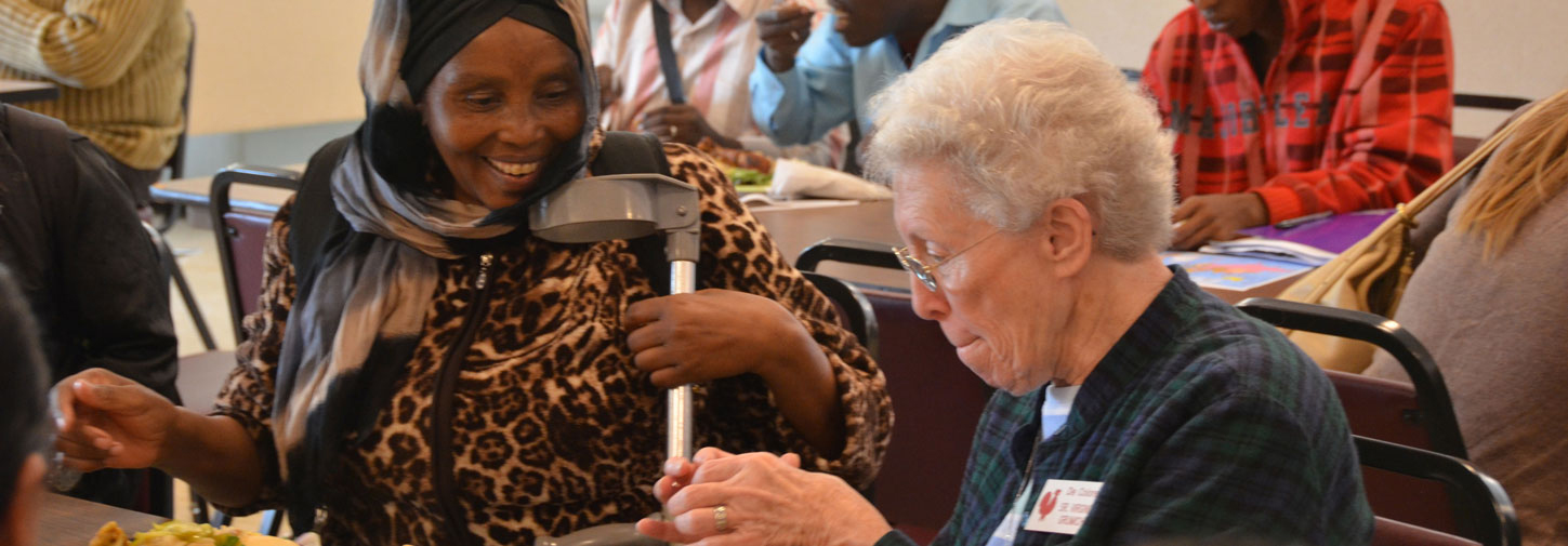 Sister Virginia Grumich chats with an immigrant from the Congo at the International Institute Luncheon