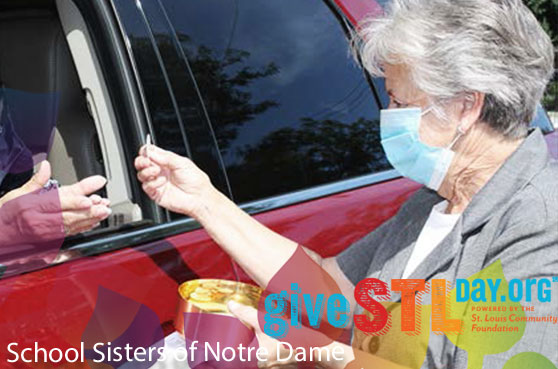 Sister Janice Munier hands out communion to a parishioner in their car in St. Louis. The image contains the Give STL Day logo, School Sisters of Notre Dame and boardered by Jubilee 2021 logo image.