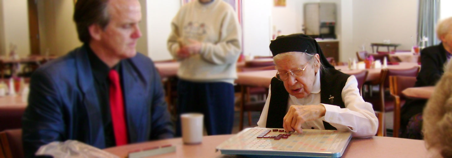 Dr. Snowdon plays scrabble with a group of sisters in Elm Gove, Wisconsin.