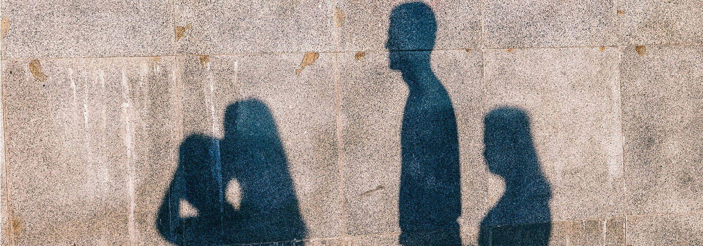Image is shadows on a brink wall of a man and three women.