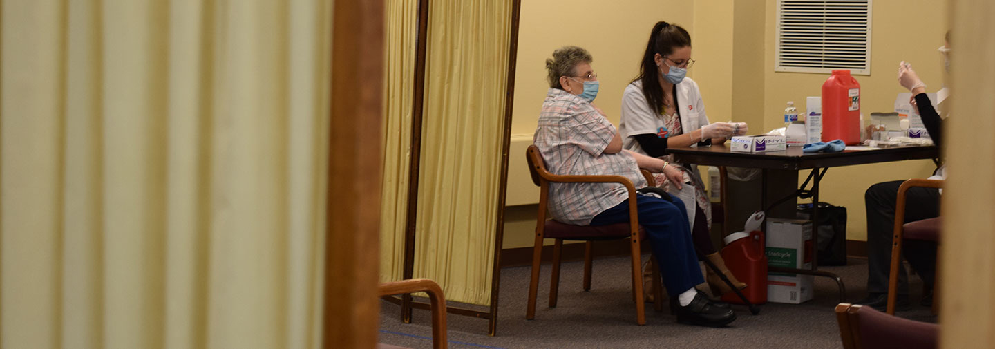 Sister works with Walgreen pharmacist to get her COVID-19 vaccine at Notre Dame of Elm Grove, Elm Grove, Wisconsin.
