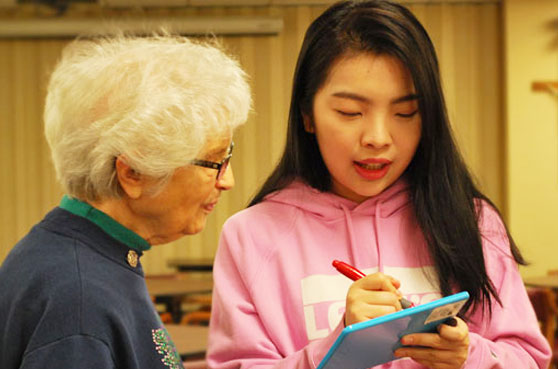A photo with Sister Sister Gina Redig and Sin Leng Lei discuss art through writing on a dry erase board while at Notre Dame Elm Grove, Elm Grove, Wisconsin.