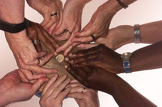 Hands from all diversity come together, holding a peace bowl at a conference in 2017 to Stand Against Racism.