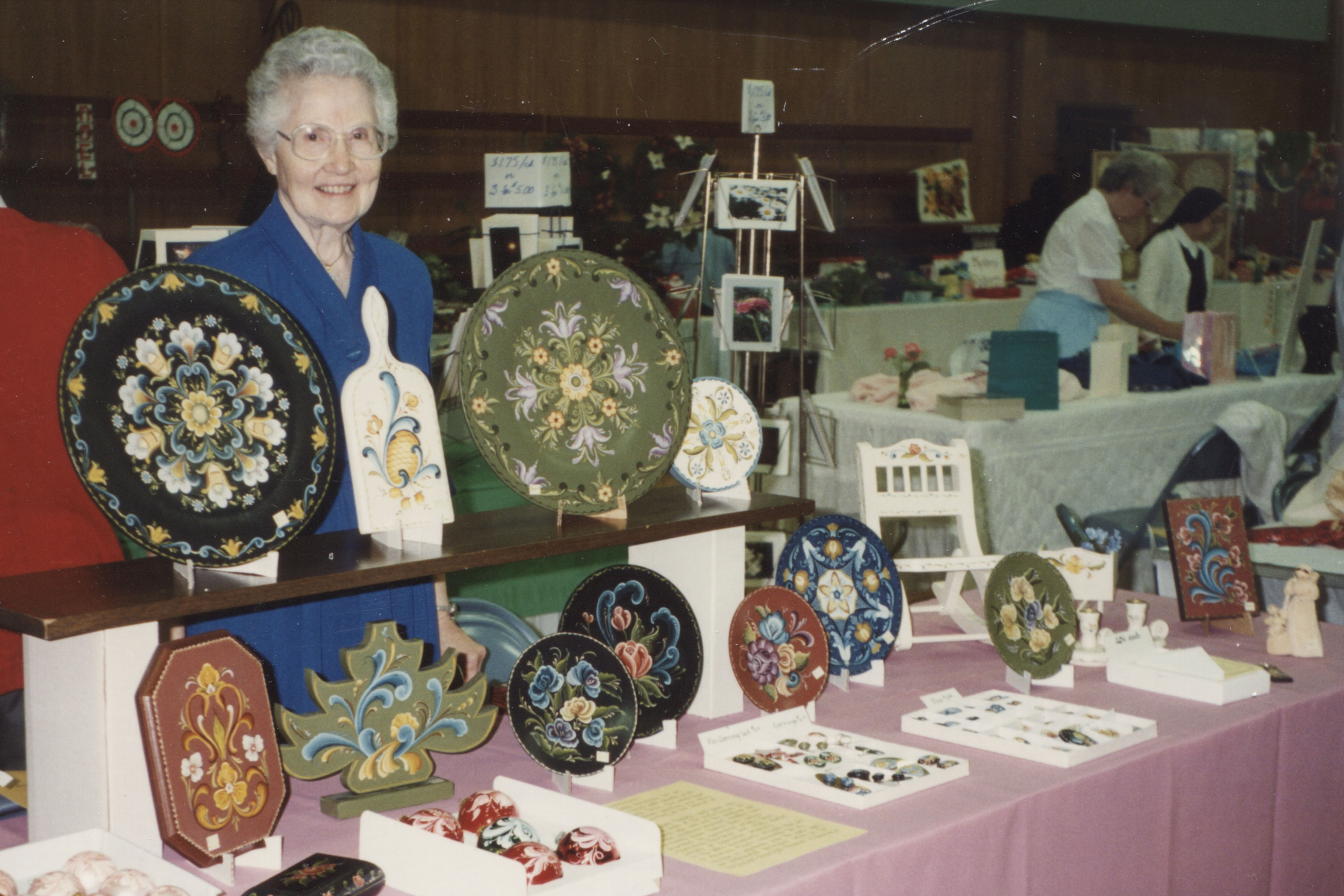 Sister Mercita Reinbold displays her rosemaling wares at the 1994 Craft Fair, held in the Loyola High School gym.