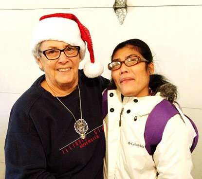 "Sister Adiare Lassonde and a reciepient of MORE's services pose for a photo during the Holiday season of ""gift giving."""