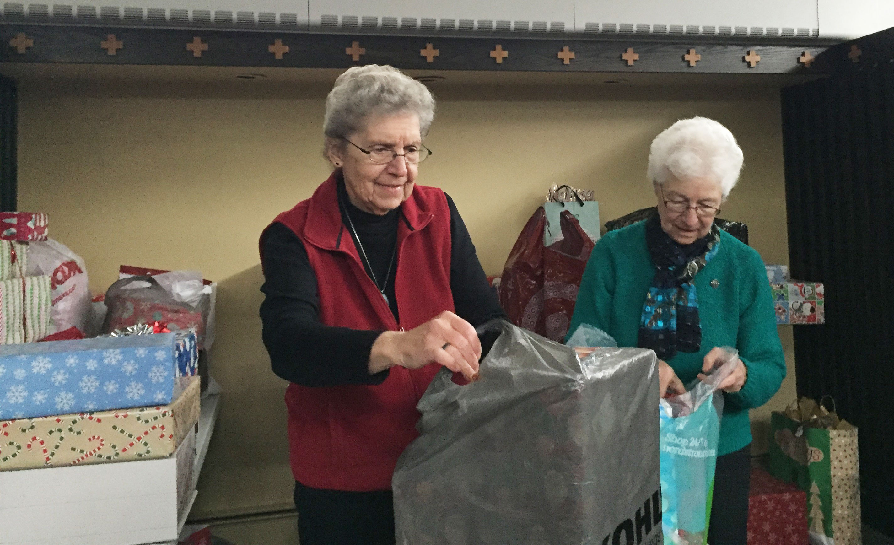 Sisters Rita Jirik and Paulissa Jirik volunteer at the Theresa Living Center (TLC) in St. Paul, Minnesota, during the holiday season. They are wrapping gifts for the clients of TLC.