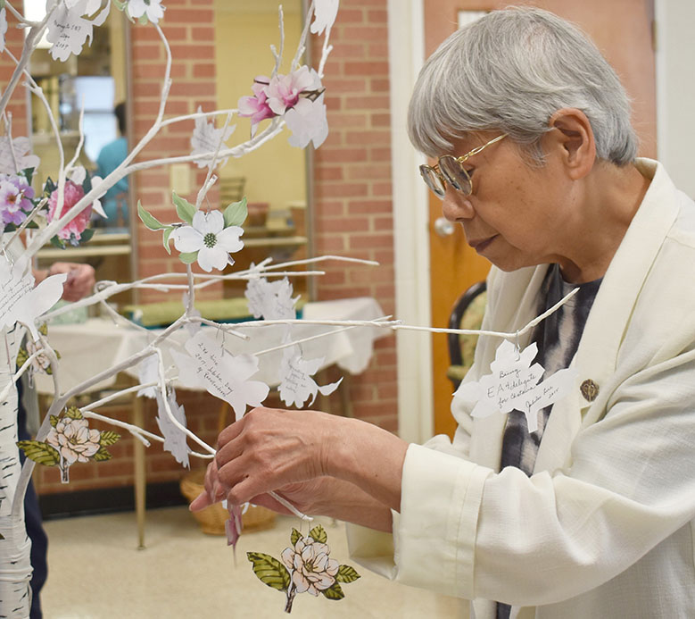 Sister Canisia Hyodo places her memory of St. Mary of the Pines on the memory tree during the Celebration of Gratitude and Farewell to 145 Years of SSND Presence at Chatawa.