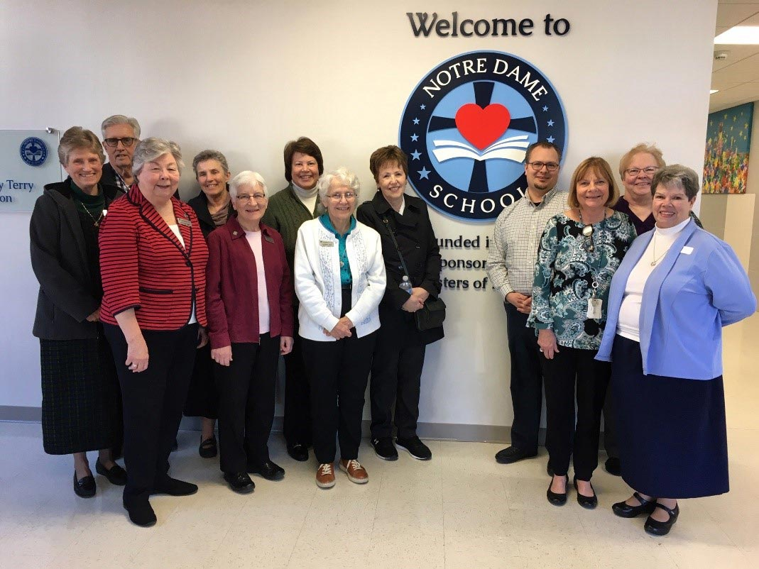The Ministry Commission gather at Notre Dame of Dallas school in front of their welcome sign. Eileen Schwalbach is in back row, third from right next to the sign.