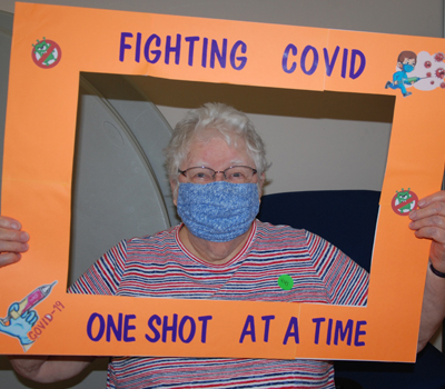 """Sisters at Our Lady of Good Counsel, Mankato, Minnesota, recieve the COVID-19 vaccine. They hold up a picture that says, """"fighting COVID one shot at a time."""