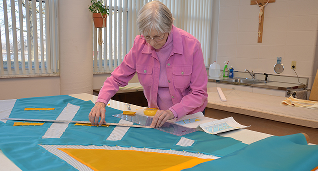 Sister Josephine Neimann working on fabric for Liturgical Fabric Arts at Sancta Maria in Ripa, St. Louis.