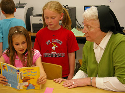 Sister sits with two students reviewing a book.