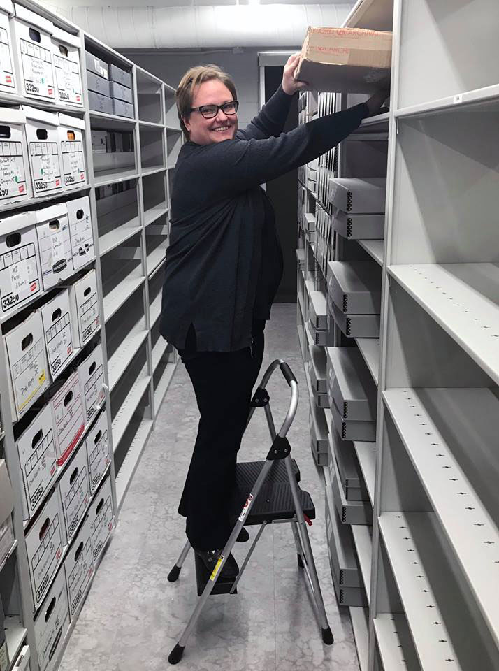Archivist Michele Levandoski puts the last box onto the shelves in the new North American Archives.