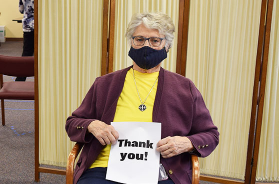 Sister recieves her COVID-19 vaccine at Notre Dame of Elm Grove, Elm Grove, Wisconsin. She holds up a thank you sign.